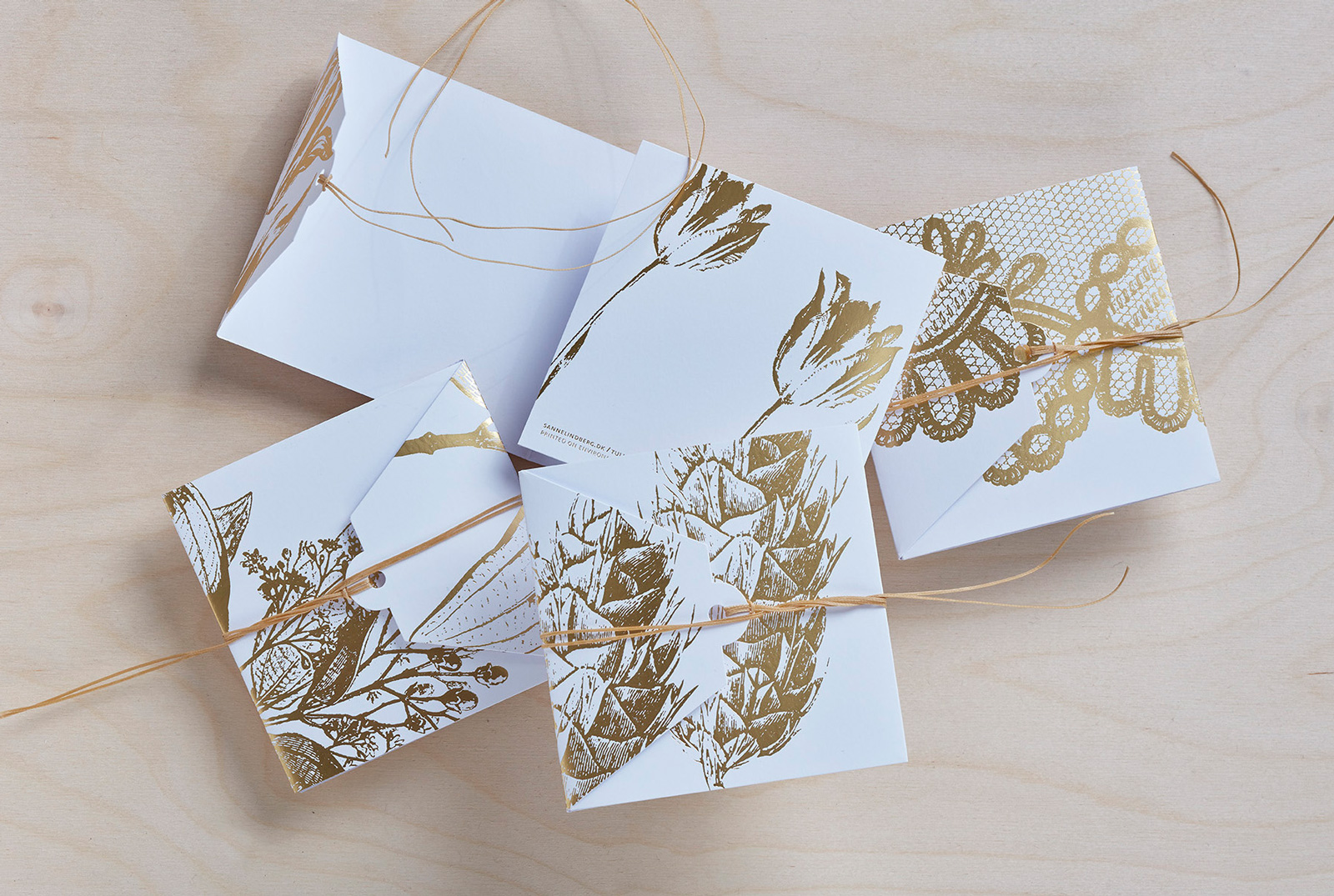 Sanne Lindberg Cards in GOLD. Shiny, embossed GOLD on crispy white. The cards measure, when folded; 12 cm x 12 cm. Folds out to triple size.