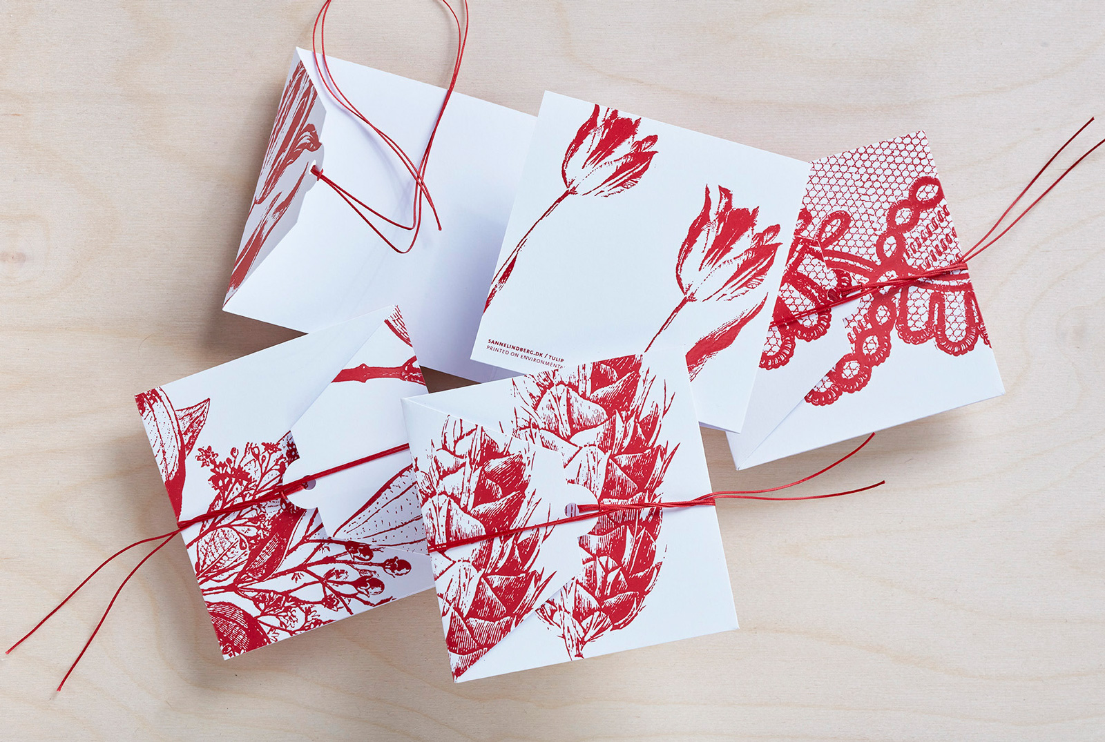Sanne Lindberg Cards in DEEP RED. Shiny red laquer on crispy white. The cards measure, when folded; 12 cm x 12 cm. Folds out to triple size. The cards are sold with envelope and wrapped in cellophane.